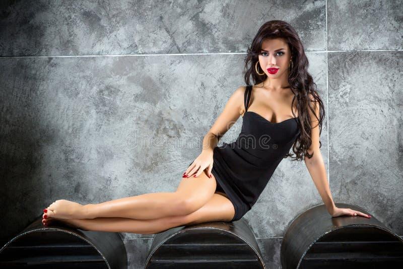 Stående av den sexiga kvinnan på en mörk metallisk bakgrund arkivfoto