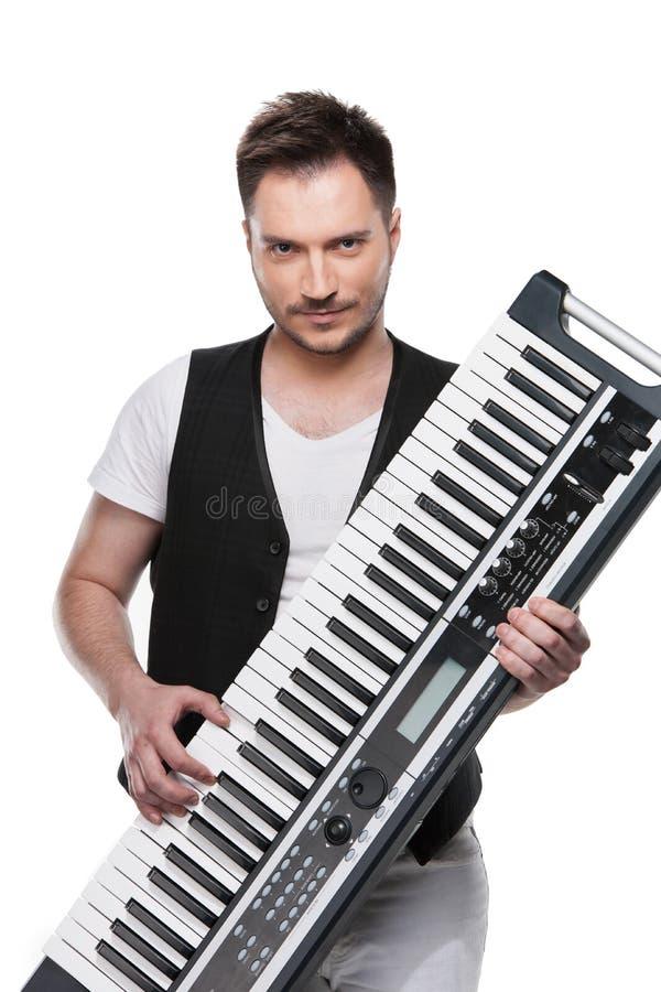 Stående av den sexiga mogna mannen med pianotangentbordet. royaltyfria foton
