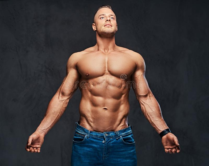 Stående av den shirtless muskulösa mannen i jeans arkivfoto