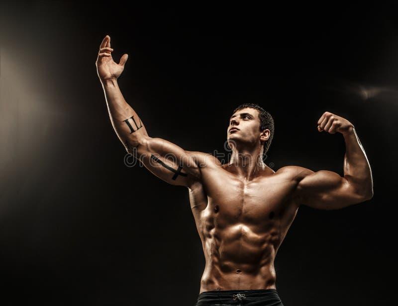 Stående av den shirtless muskulösa mannen med armen upp arkivfoton