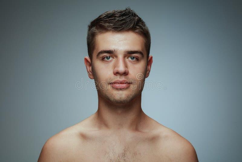 Stående av den shirtless unga mannen som isoleras på grå studiobakgrund arkivbilder
