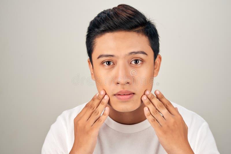 Stående av den shirtless unga stiliga asiatiska mannen som kontrollerar hans framsida för begrepp för hudomsorg och skönhet royaltyfri foto
