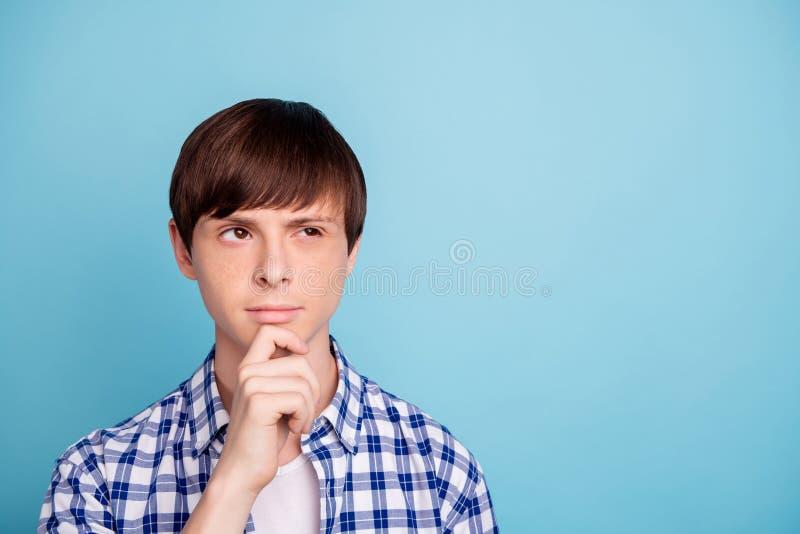 Stående av den sinnade pojken som trycker på hakan med hans fingrar som ser den iklädda kontrollerade skjortan över blå bakgrund royaltyfria bilder