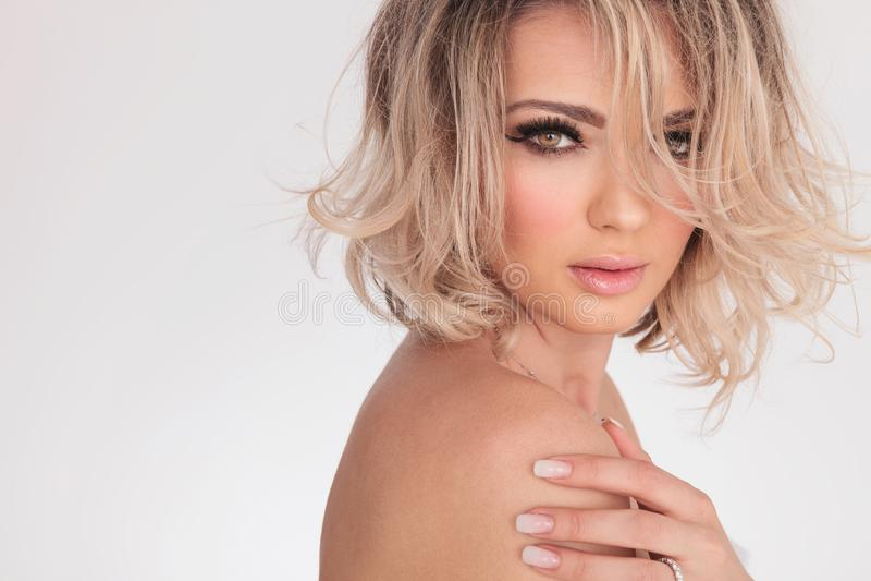 Stående av den sinnliga nakna blonda kvinnan som trycker på hennes skuldra fotografering för bildbyråer