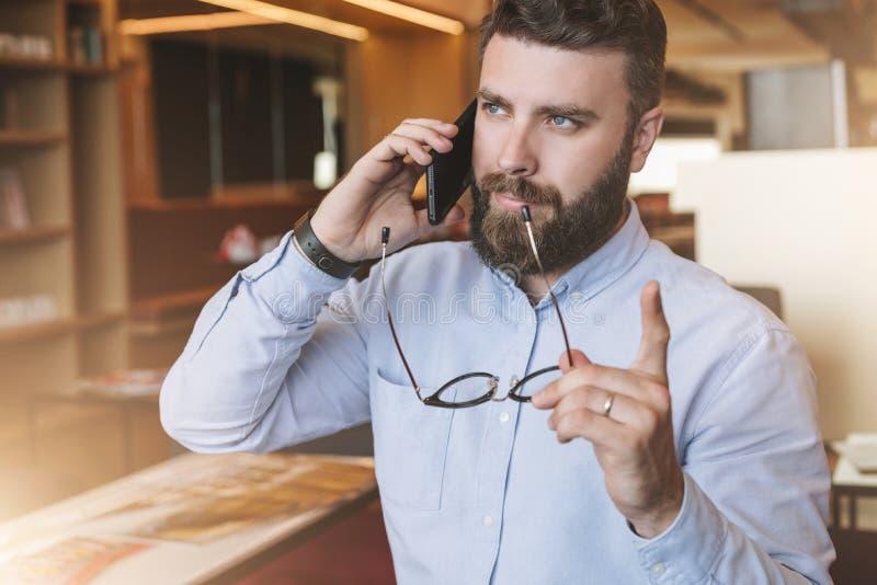 Stående av den skäggiga affärsmannen i skjortan, hållande exponeringsglas i handen som lyfter upp hans pekfinger och talar på mob fotografering för bildbyråer