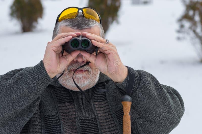 Stående av den skäggiga Caucasian höga mannen som ser till och med kikare på vintersäsongen royaltyfria foton