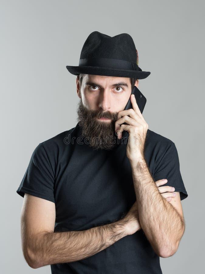 Stående av den skäggiga hipsteren som bär den svarta hatten och t-skjortan som talar på telefonen som ser kameran royaltyfri bild