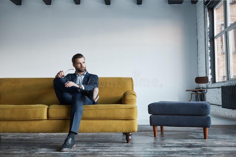 Stående av den skäggiga och stiliga affärsmannen i modedräkten som vilar på soffan i ett modernt kontor och ser in royaltyfria foton
