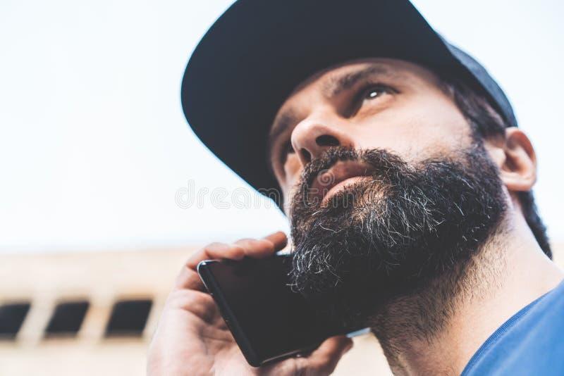 Stående av den skäggiga stiliga mannen som använder hans smartphone på gatan suddighet bakgrund horisontal Visuella effekter royaltyfri foto