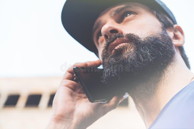 Stående av den skäggiga unga mannen som använder hans smartphone på gatan suddighet bakgrund horisontal Visuella effekter royaltyfri fotografi