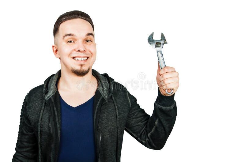 Stående av den skäggiga unga mannen som rymmer den justerbara skiftnyckeln bakgrund isolerad white arkivfoto