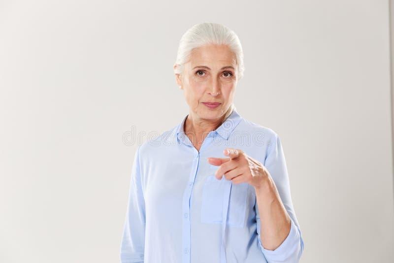 Stående av den skämtsamma äldre kvinnan som pekar med fingret till dig arkivfoto