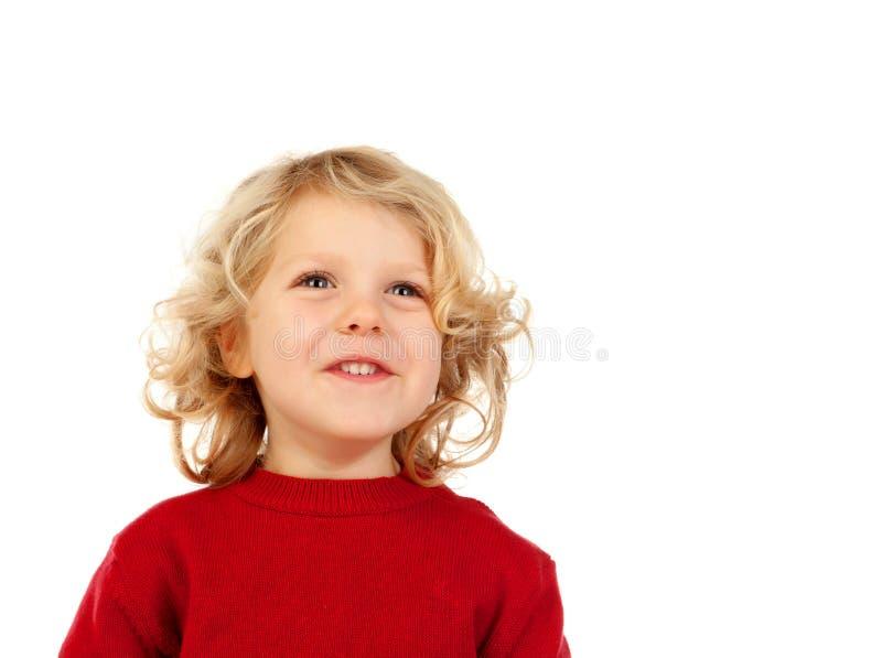 Stående av den skämtsamma lilla ungen med långt blont hår som ser upp royaltyfria foton
