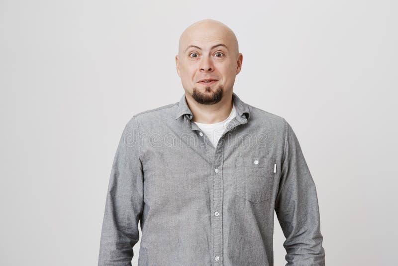 Stående av den skalliga mogna mannen med skägget som ser förvånat och förbluffat på kameran, medan stå över vit bakgrund arkivfoton