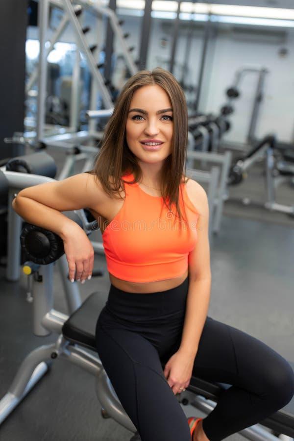 Stående av den slanka stiliga unga kvinnan att koppla av i idrottshall efter hård utbildning royaltyfri bild