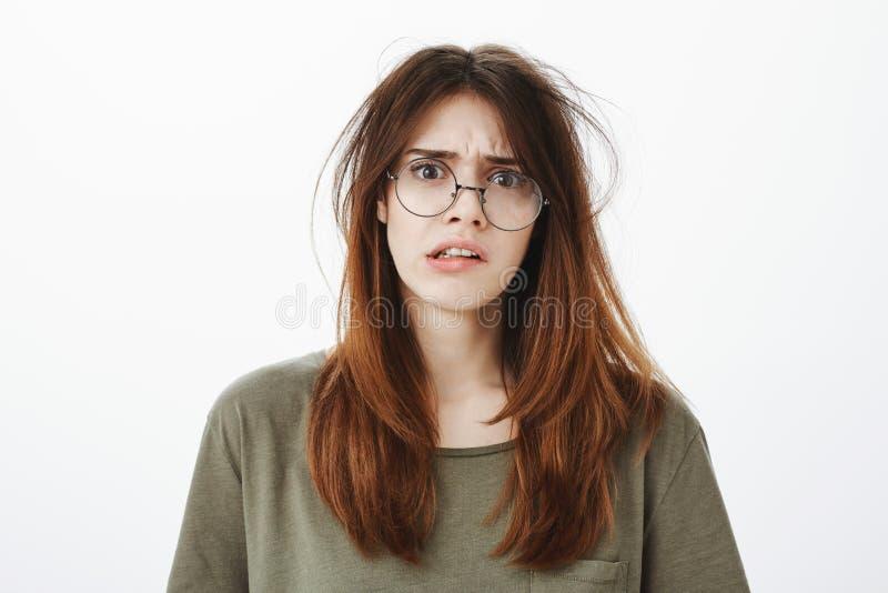 Stående av den slarviga roliga nerdy kvinnan i moderiktiga genomskinliga exponeringsglas med smutsigt hår som ser förvirrad och u arkivfoto