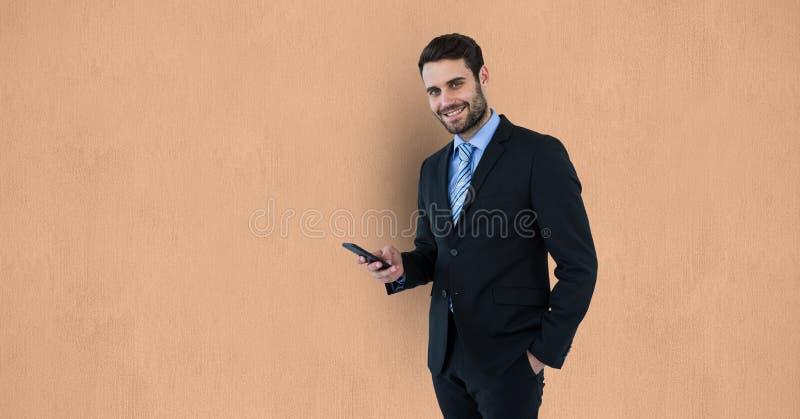 Stående av den smarta telefonen för affärsmaninnehav över beige bakgrund royaltyfria foton