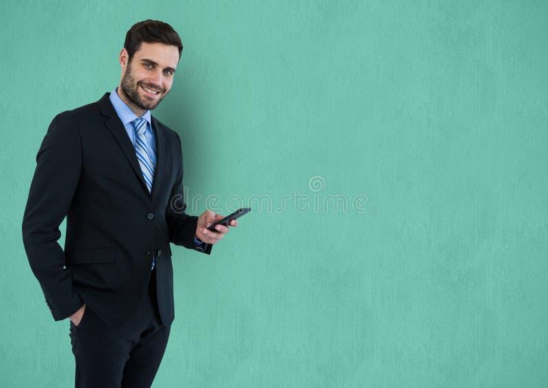 Stående av den smarta telefonen för affärsmaninnehav över turkosbakgrund royaltyfria foton