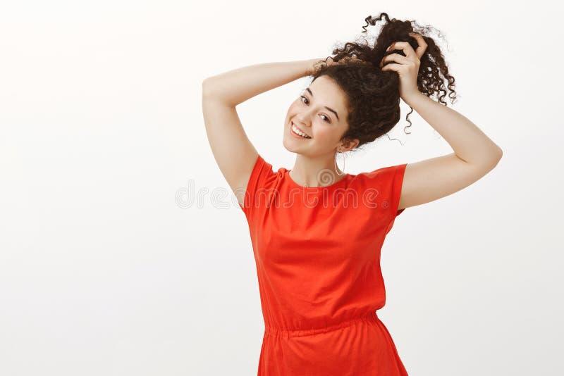 Stående av den snygga glade europeiska kvinnan i moderiktig tillfällig röd klänning som lyfter händer och kammar lockigt hår i bu royaltyfri foto