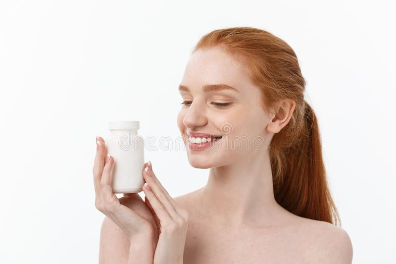 Stående av den snygga unga caucasian kvinnan som rymmer piller som försöker att ta omsorg av immunförsvaret och hälsa över grå fä royaltyfri foto
