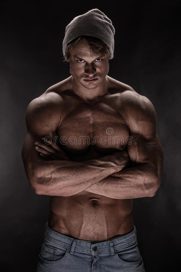 Stående av den starka idrotts- konditionmannen över svart bakgrund arkivbilder