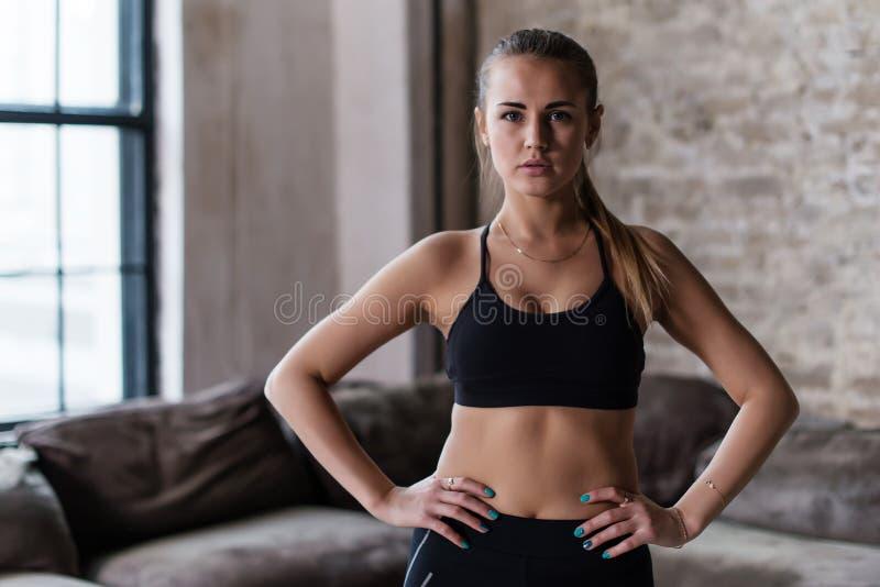 Stående av den starka slanka sportiga Caucasian unga idrottskvinnan som bär svart sportbehåanseende med händer på att se för höft royaltyfri fotografi