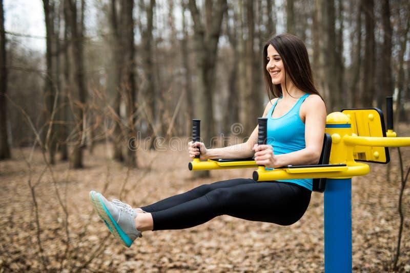 Stående av den starka unga kvinnan som hänger på ribbstol med hennes ben upp Konditionkvinnan som utför det hängande benet, lyfte arkivbild