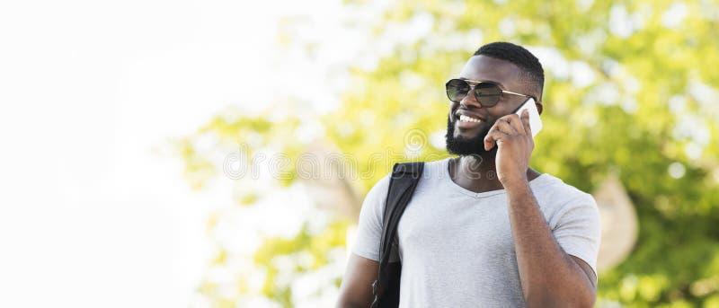 Stående av den stilfulla afrikanska mannen i solexponeringsglas som talar vid telefonen arkivbild