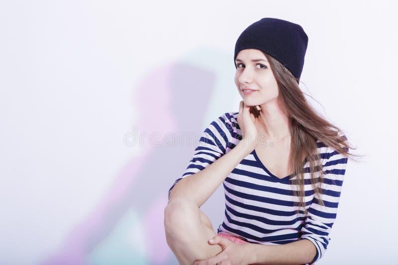 Stående av den stilfulla Caucasian brunetten i hatten som poserar på den vita asken i studio arkivbilder