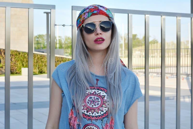 Stående av den stilfulla glamorösa unga kvinnan som bär stor svart solglasögon och hippiestilkläder royaltyfria bilder