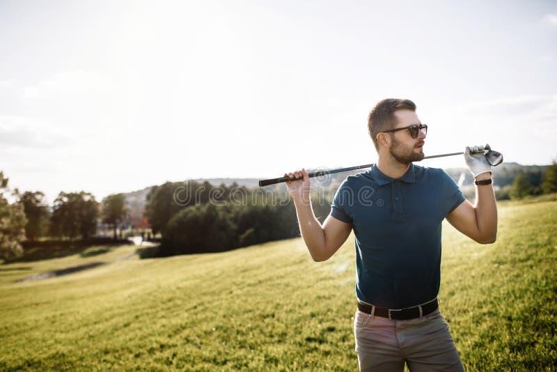 Stående av den stilfulla golfaren i exponeringsglas som står på golfbanawi arkivbilder
