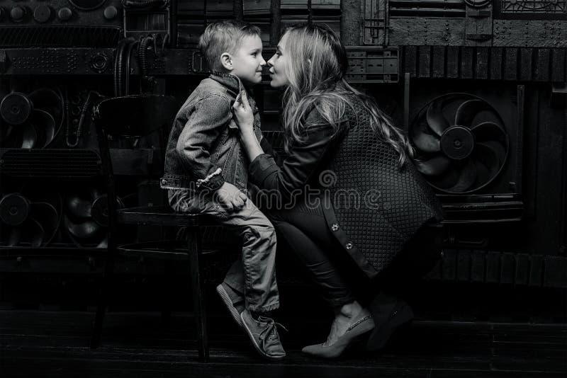 Stående av den stilfulla gulliga pysen med den härliga mamman arkivbilder