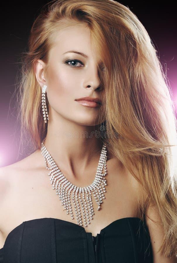 Stående av den stilfulla kvinnan med härligt hår och lyxsmycken royaltyfria foton