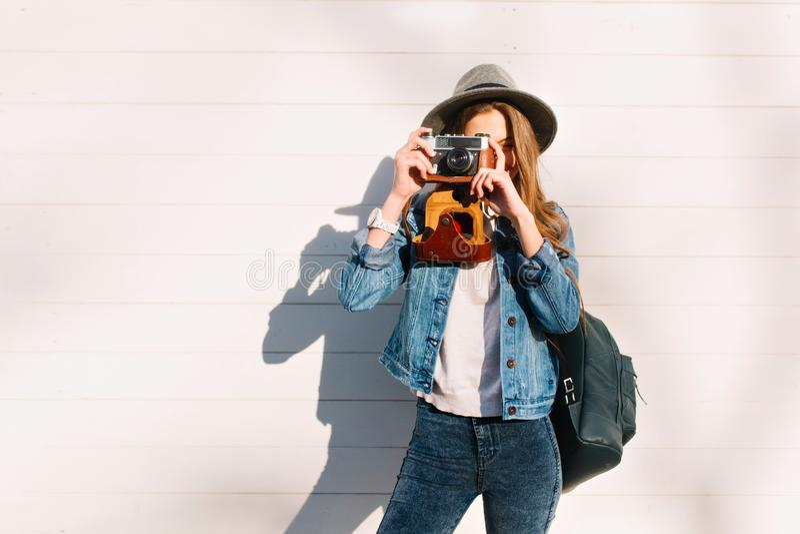 Stående av den stilfulla kvinnliga fotografen i den moderiktiga hatten som utanför poserar med den yrkesmässiga kameran Charma br arkivbilder