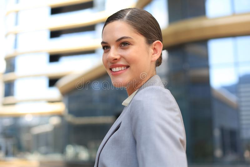 Stående av den stilfulla le affärskvinnan i trendig kläder i storstaden som purposefully bort ser arkivbild