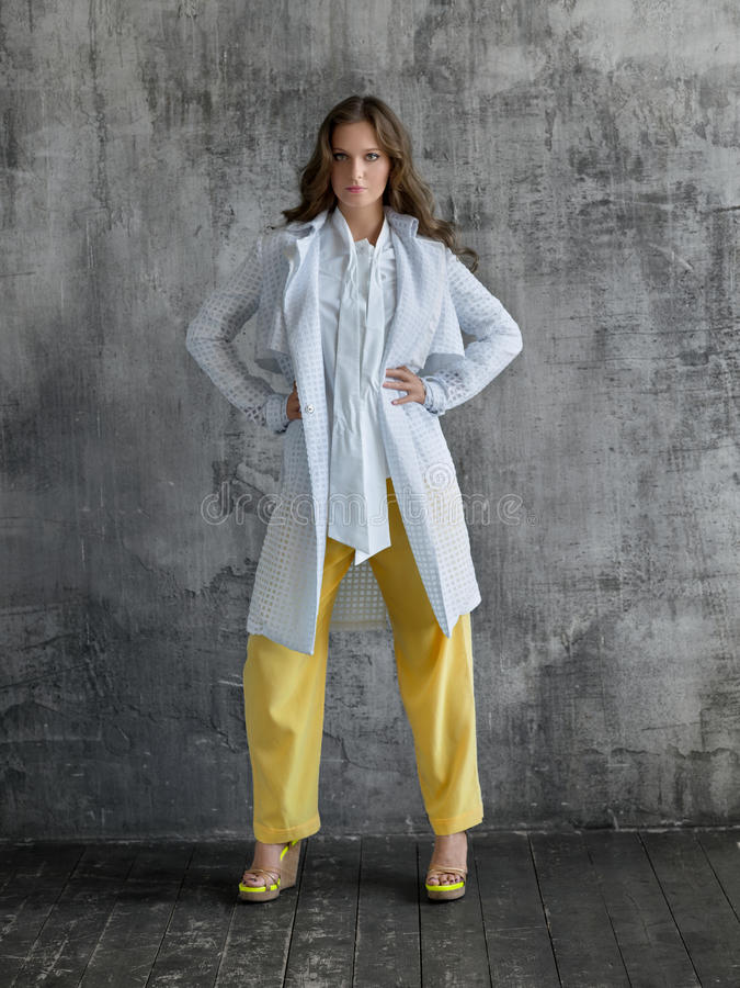 Stående av den stilfulla unga kvinnan i den vita skjortan, gul byxa och lag arkivbild