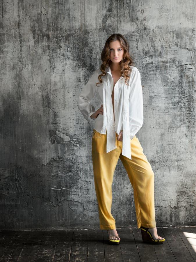 Stående av den stilfulla unga kvinnan i den vita skjortan och gul byxa royaltyfria bilder