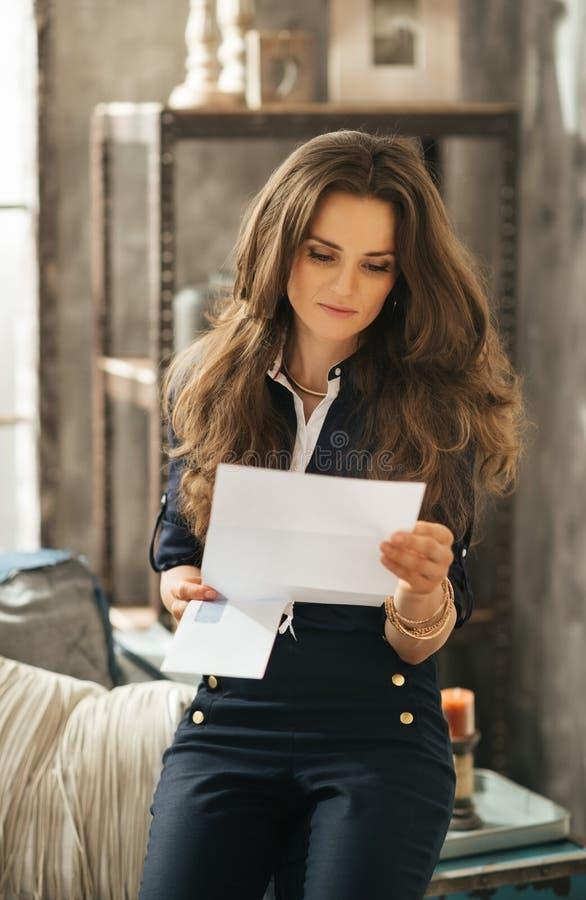 Stående av den stilfulla unga kvinnan med bruna hår som läser brevet royaltyfri fotografi