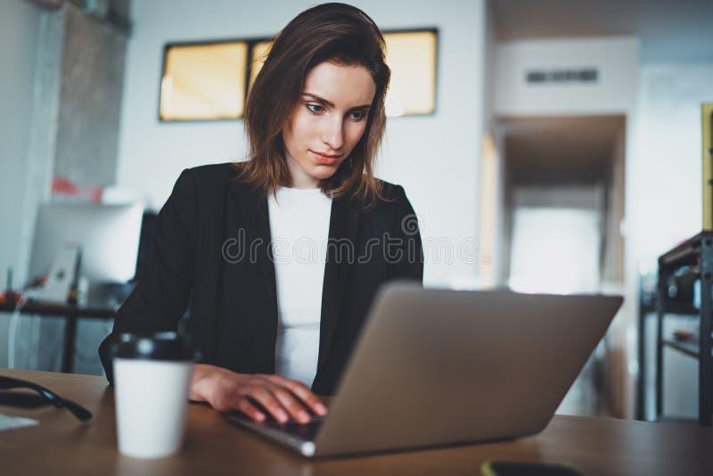 Stående av den stiliga affärskvinnan som använder bärbar datordatoren på det moderna kontoret suddighet bakgrund horisontal royaltyfria bilder