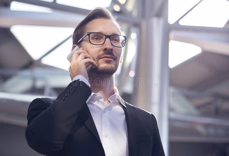Stående av den stiliga affärsmannen i dräkt och glasögon som talar på telefonen i flygplats royaltyfri foto