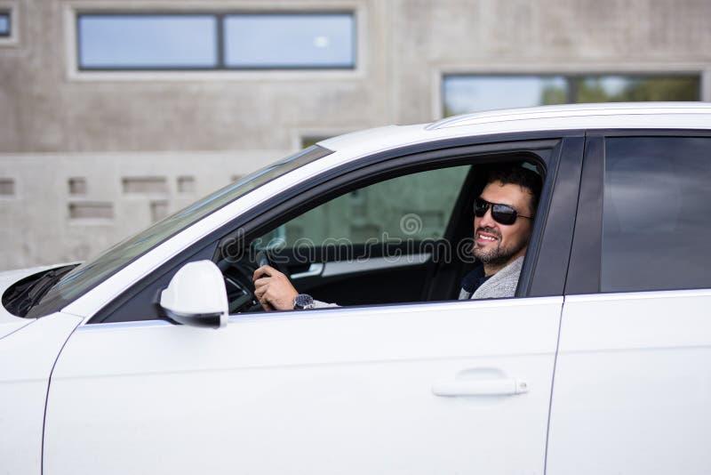 Stående av den stiliga affärsmannen som sitter i bil royaltyfri foto