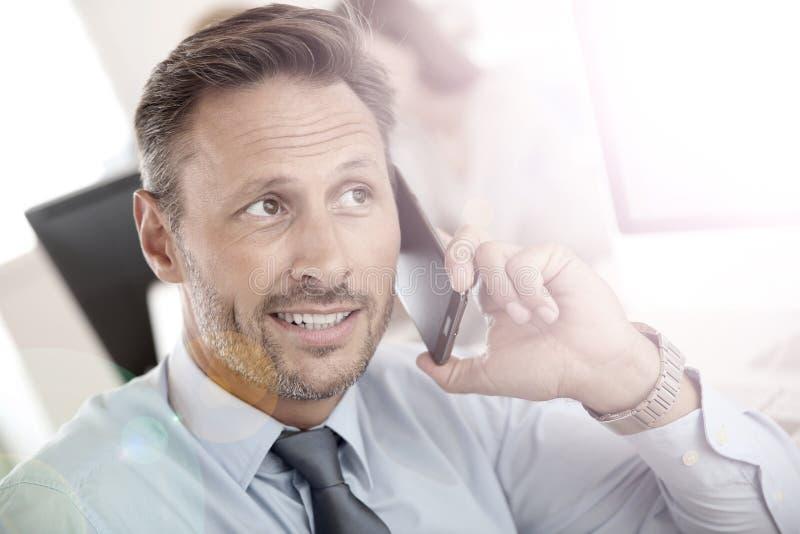 Stående av den stiliga affärsmannen som talar på smartphonen royaltyfri bild