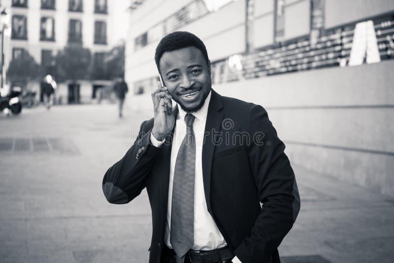 Stående av den stiliga afrikansk amerikanaffärsmannen som går i staden som talar på mobiltelefonen royaltyfri bild
