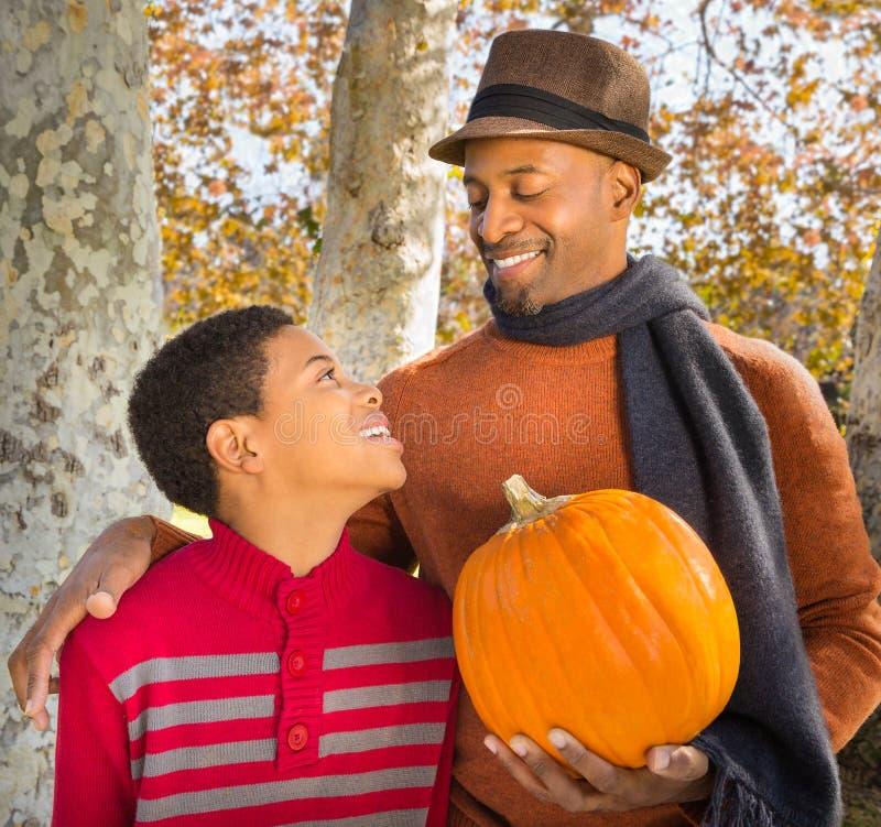 Stående av den stiliga afrikansk amerikanfadern och lyckliga sonen som väljer en pumpa i höst royaltyfri foto