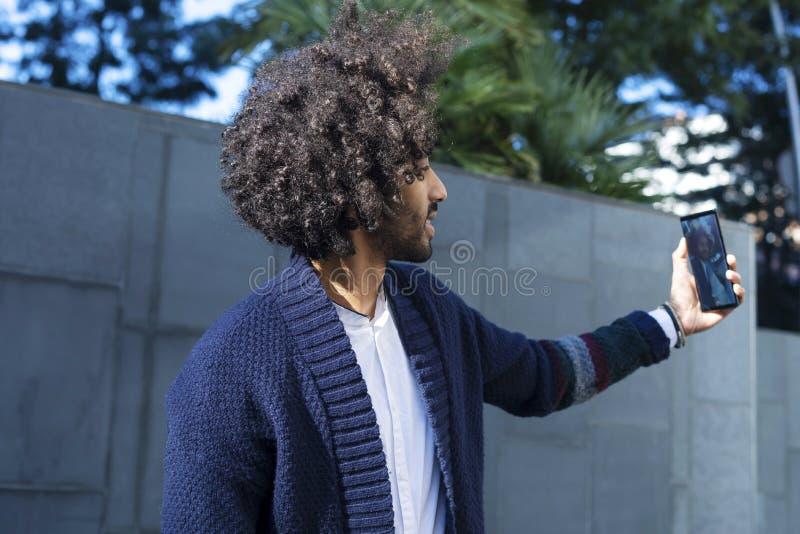 Stående av den stiliga afro- amerikanska mannen i tillfällig kläder genom att använda en mobiltelefon och le, medan ta en selfie, royaltyfri foto