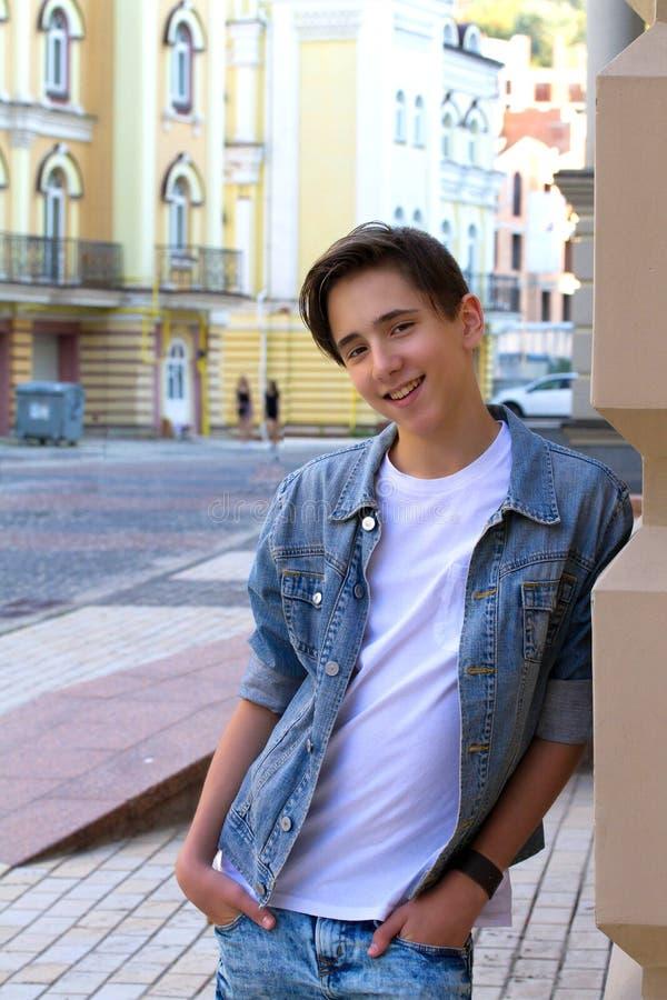 Stående av den stiliga attraktiva tonåriga pojken som utomhus ler och nästan blir den gamla väggen royaltyfria foton