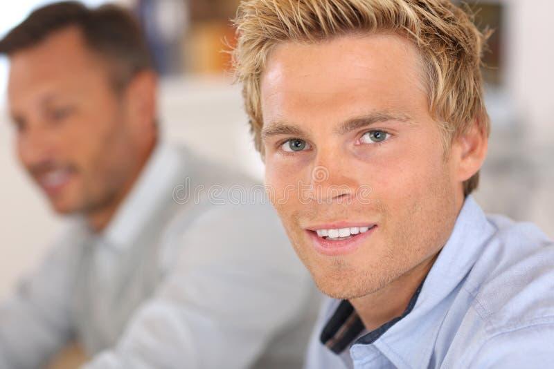 Stående av den stiliga blonda mannen under möte fotografering för bildbyråer