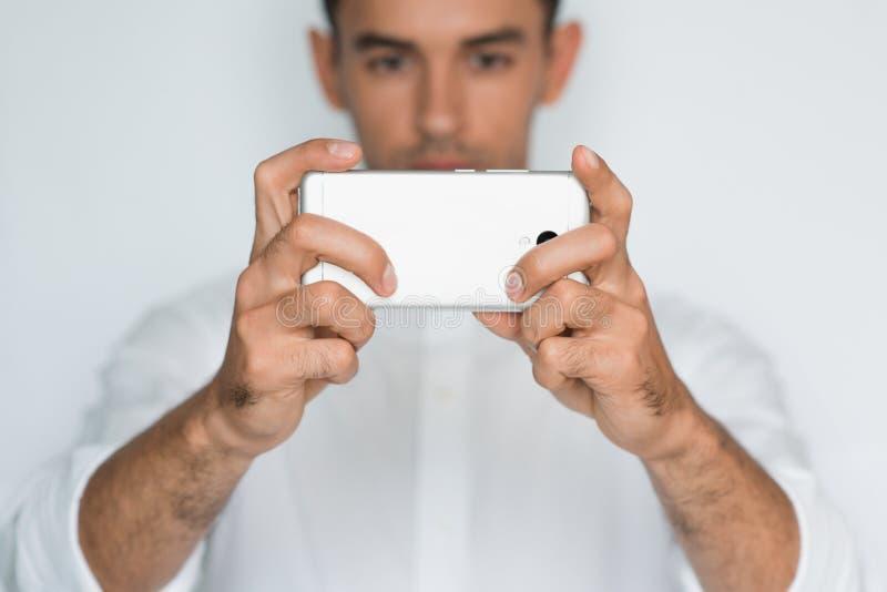 Stående av den stiliga caucasian mannen som tar en selfie med den smarta telefonen som isoleras på vit bakgrund arkivbild