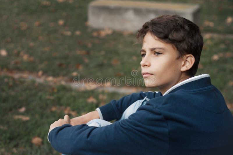 Stående av den stiliga, eftertänksamma och allvarliga tonåriga pojken utomhus grabb fotografering för bildbyråer