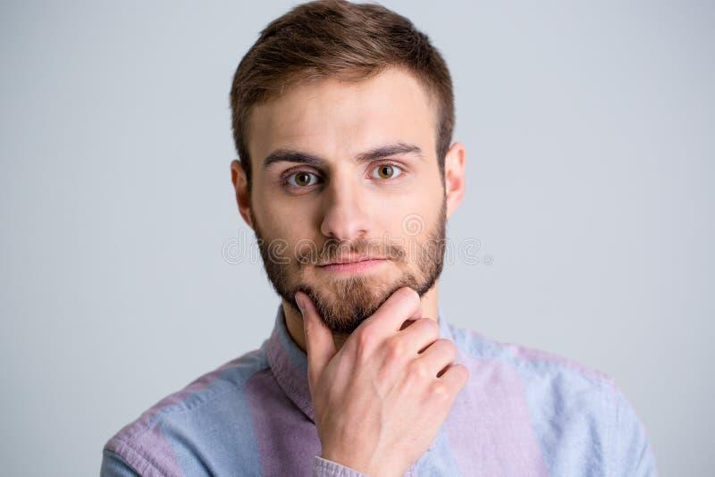 Stående av den stiliga fundersamma unga mannen med skägget fotografering för bildbyråer